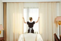stock photo hotel service female housekeeping chambermaid worker with opening curtains of window in room 315037901