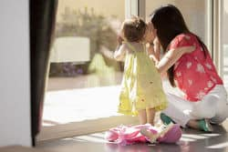 stock photo mom and daughter looking through the window 132864209